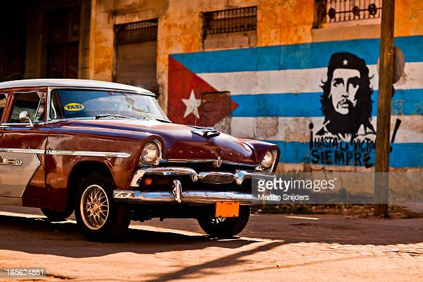 plymouth classic car passing cuban flag - old havana stock pictures, royalty-free photos & images