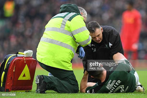 Plymouth's Scottish defender Gary Miller receives medical attention after picking up an injury during the English FA Cup third round football match...