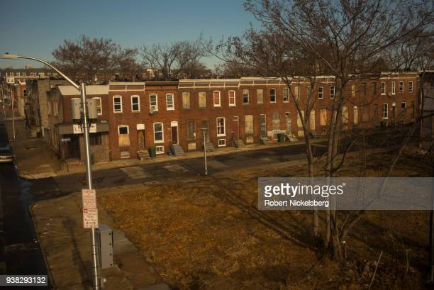 Plywood covers windows and doors in partly abandoned neighborhood along the Amtrak railroad tracks January 9 2018 in Baltimore Maryland Often named...