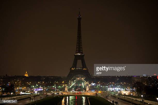 The Eiffel tower is seen before submerging into darkness at 830 pm as part of the Earth Hour switchoff on March 23 2013 in Paris Organisers expect...