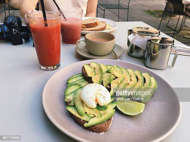 poached egg on bread with avocado slices and juices - avocado toast stockfoto's en -beelden