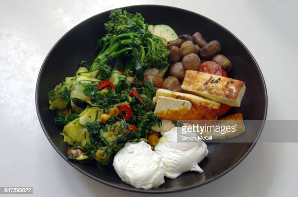 poached eggs with halloumi cheese, mushrooms, avocado, hummous, almonds, zucchini salad, kale and broccolini - low carb diet stock photos and pictures