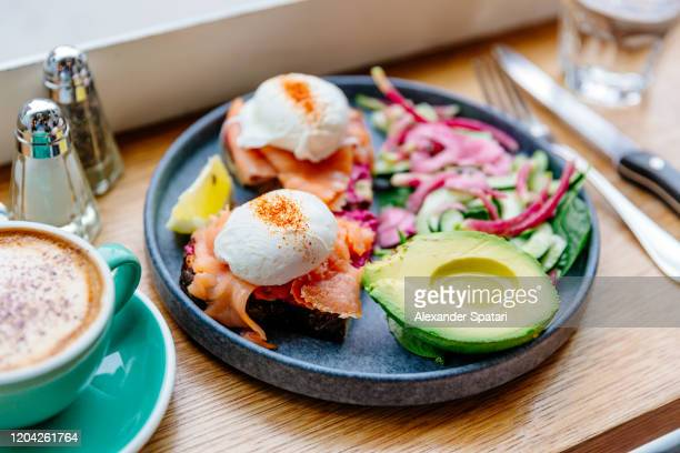 poached eggs with salmon and avocado on the plate, side view - brunch stock pictures, royalty-free photos & images