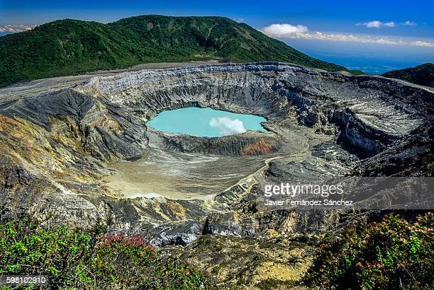 poas volcano crater with its lake and fumarole, in costa rica. an active stratovolcano that is one of the most important tourist destinations in the central american country. - acid rain stock photos and pictures