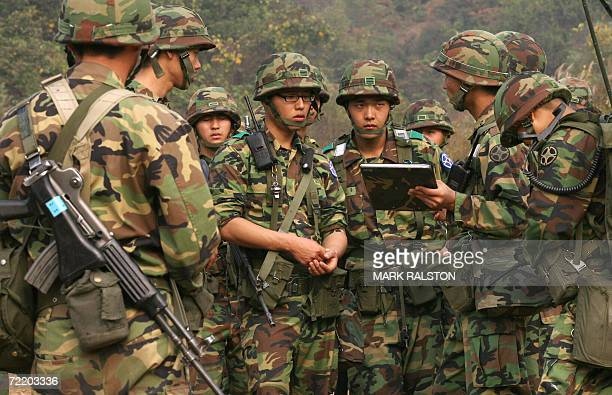 Pocheon, REPUBLIC OF KOREA: South Korean soldiers receive a briefing from an officer before a mechanized military exercise at the Yeongpyeong River,...