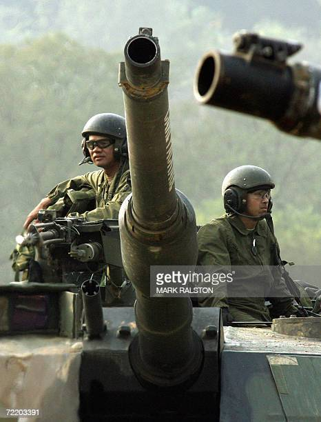 Pocheon, REPUBLIC OF KOREA: The crew of a US M1 Abraham tank takes a break after a mechanized military exercise at the Yeongpyeong River, in Pocheon...