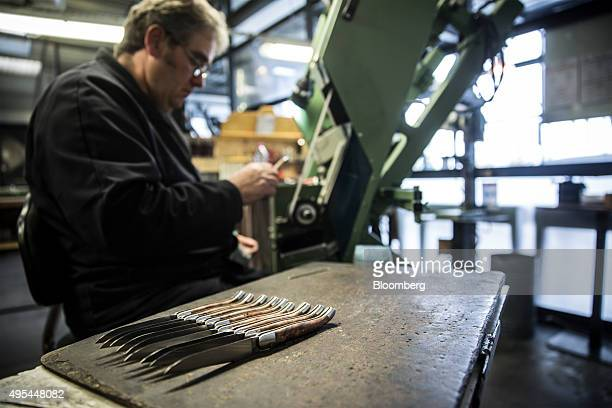 Pocket knives sit on a work bench as a cutler inspects a sanded knife handle during manufacture at Forge De Laguiole traditional knife and cutlery...