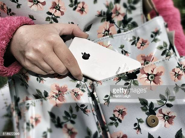 Pocket phoneiPhone 5c in front pocket of flower patterned satchel Female hand removing phone to use outdoors UK
