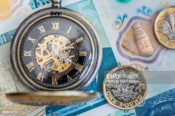 Pocket watch and pound coins on £5 note