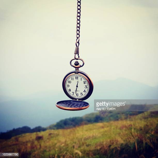 Pocket Watch Hanging Over Field Against Clear Sky