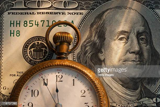 Pocket watch on one hundred dollar bill, studio shot