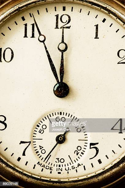 Pocket watch showing four minutes to midnight