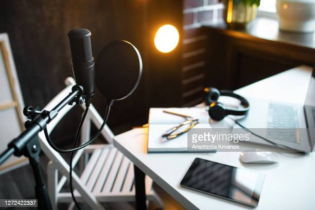 podcast streaming at home. audio studio with laptop, microphone with pop filter and headphones on white table against black wall with warm lights. blogger concept. - radio stock pictures, royalty-free photos & images