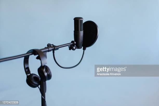 podcast streaming at studio. microphone on stand with pop filter and headphones on blue background. blogger concept. - radio broadcasting stock pictures, royalty-free photos & images
