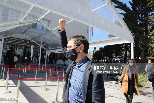 Podemos co-founder Juan Carlos Monedero raises his arm as he leaves the Plaza de Castilla courts after testifying as defendant for alleged irregular...