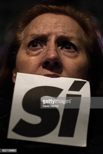Podemos supporter bites a ballot that it reads 'Si' as she wathc on a huge screens the first exit poll results at a Podemos gathering on December 20...