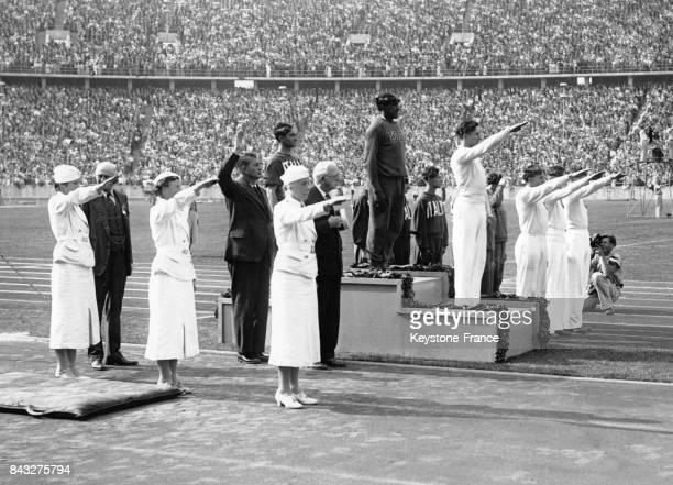 Podium olympique du 4x100 mètres médailles d'or équipe des EtatsUnis avec Jesse Owens argent équipe d'Italie et bronze équipe d'Allemagne à Berlin...