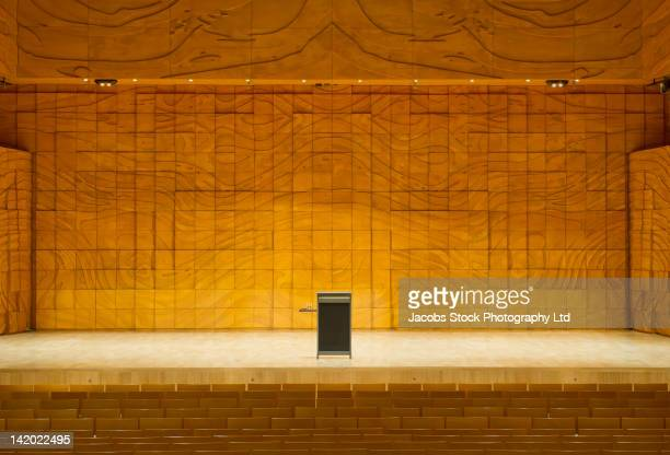 podium on stage in empty auditorium - zuschauerraum stock-fotos und bilder