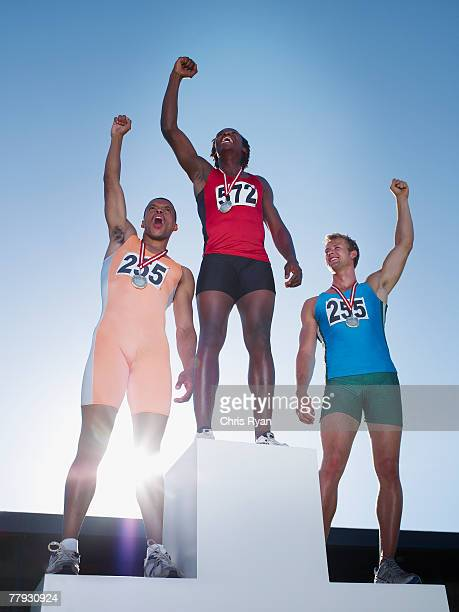 podium with three winning athletes cheering on it - medal stock pictures, royalty-free photos & images