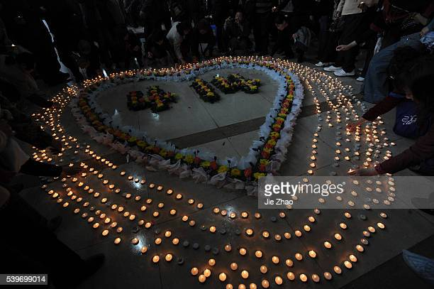 Poeple burn candles during an activity to mourn the victims who died during the Apri 14 Yushu earthquake of Qinghai province at a university of Wuhan...