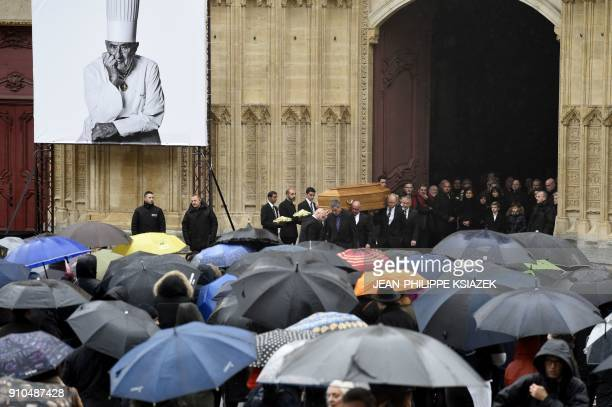 Poeple look at the coffin of French chef Paul Bocuse as it leaves the SaintJean Cathedral in Lyon on January 26 2018 at the end of the funeral...