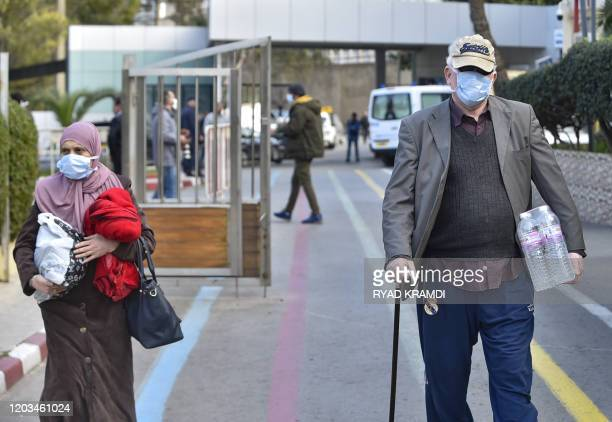 Poeple waering wearing protective masks walk out of the ElKettar hospital in the Algerian capital Algiers on February 26 2020 Algerian authorities...