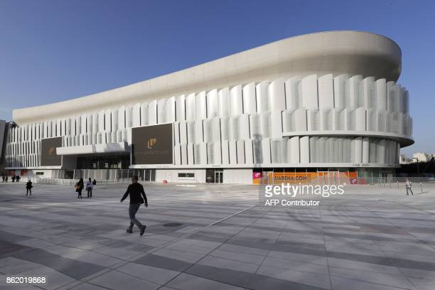 Poeple walk near the U Arena in Nanterre west of Paris during its official inauguration on October 16 2017 The U Arena is the new largest covered...