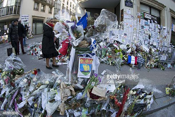 Poeple walk outside the headquarters of French satirical weekly Charlie Hebdo in Paris on February 7 next to flowers layed in memory of victims one...