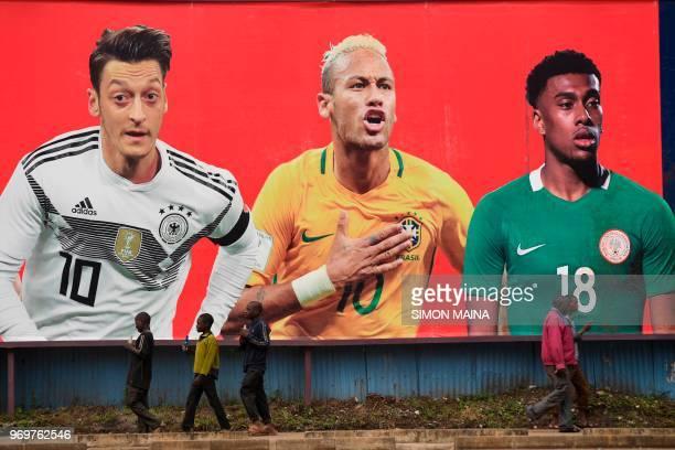 Poeple walk past a football billboard displaying Germany's midfielder Mesut Ozil Brazil's striker Neymar and Nigeria's midfielder Alex Iwobi on June...