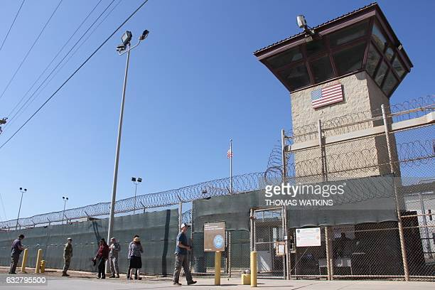 Poeple walk past a guard tower outside the fencing of Camp 5 at the US Military's Prison in Guantanamo Bay Cuba on January 26 2017 President Donald...