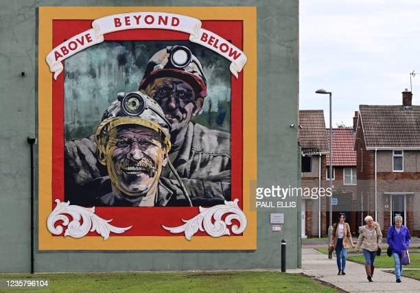 Poeple walk past a mural tribute to the miners of Seaham painted by artist Cosmo Sarson titled 'Above Beyond Below', painted on the gable end of the...