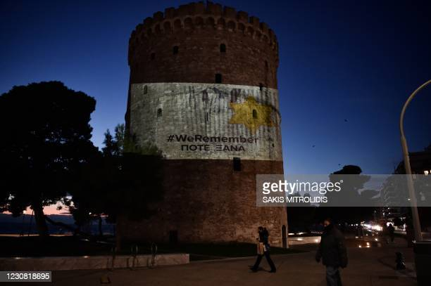 Poeple walk past a projection on the facade of White Tower of Thessaloniki depecting the concentration camp uniform jacket with the yellow star and...