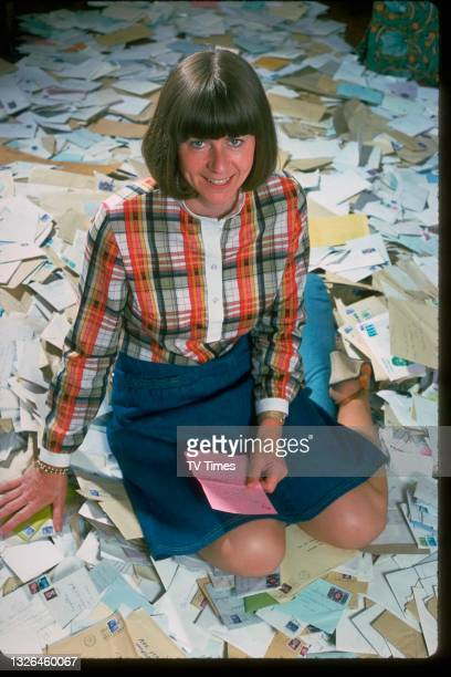 Poet and comedian Pam Ayres photographed with an enormous pile of letters for the cover of TV Times Magazine, circa August 1977.