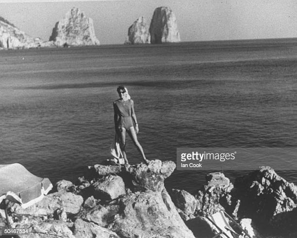 Poet Anne Sexton in onepiece bathing suit standing on rocks at shore w ocean in bkgrd