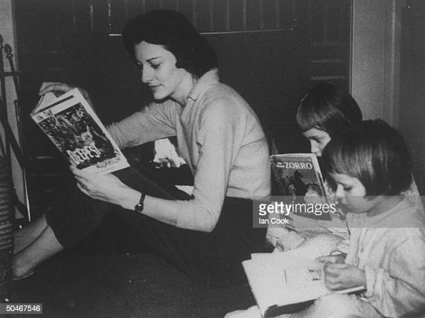 Poet Anne Sexton sitting on floor in front of fireplace reading a book as her daughters Joy Linda sit next to her reading books at home
