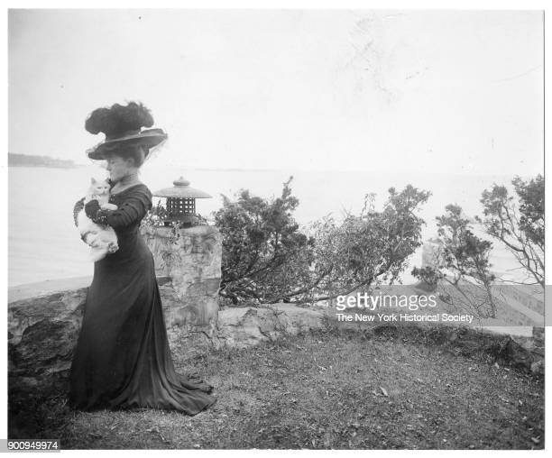 Poet Ella Wheeler Wilcox in large hat with feathers and veil holding cat to her chest next to a short stone wall at edge of cliff overlooking water...