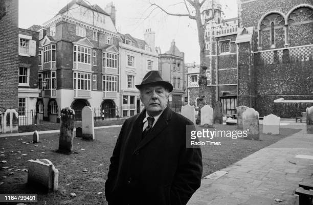 Poet Laureate John Betjeman in the churchyard of St Bartholomew the Great near his home, interviewed for the BBC television documentary 'Thank God...