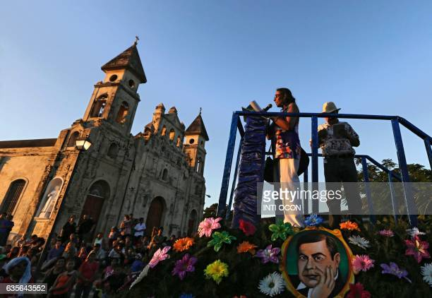 A poet reads her work on a stage where a portrait of famous Nicaraguan poet Ruben Dario is displayed during the XIII Poetry Festival in Granada some...