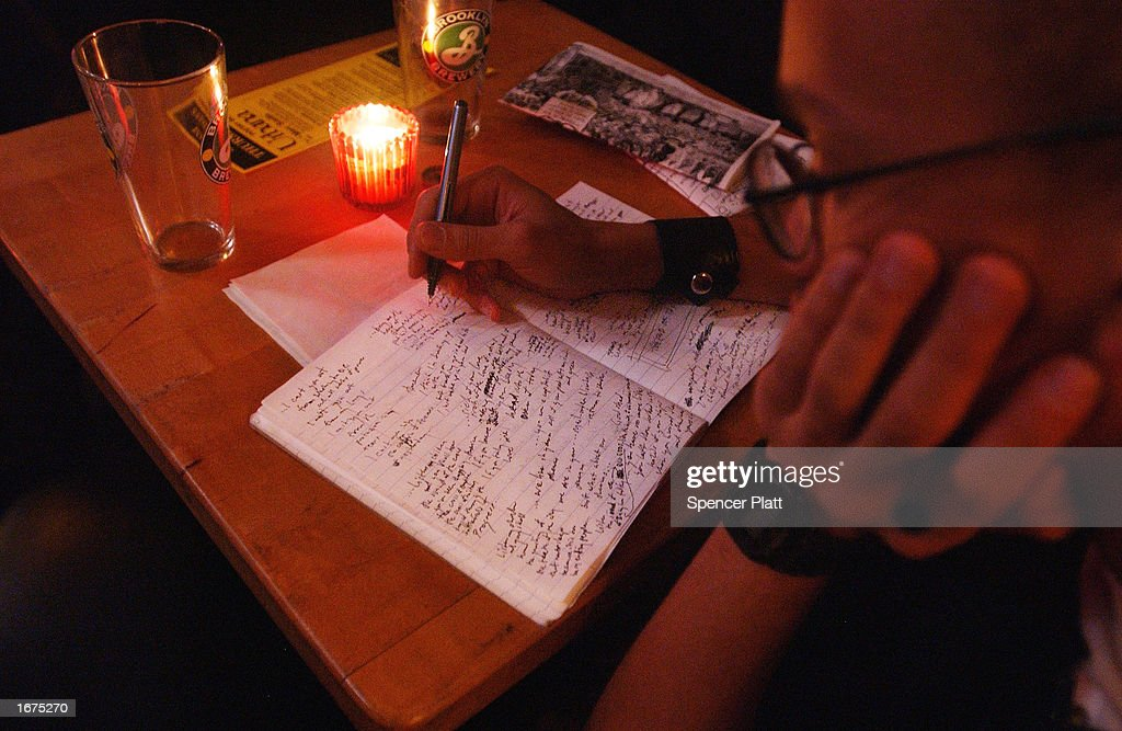 A poet writes before a poetry performance at the Bowery