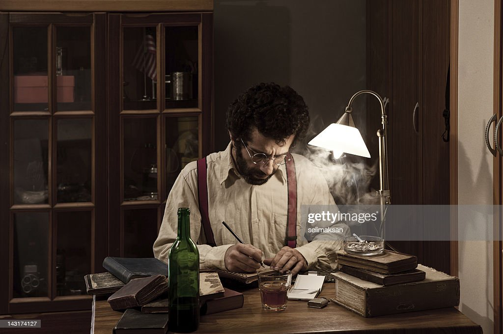 Poet writing on table in the dark : Stock Photo