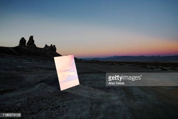 poetic picture of mirror reflecting sunset sky in the middle of desert in california. - 鏡 ストックフォトと画像