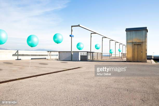 Poetic picture of stop motion pictures in one of a line of green balloons flying in city corner with nice perspective.