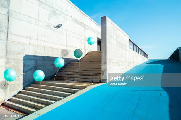 poetic stop motion picture of green balloons following each other going up on stairs in a minimal and cool architecture corner in the city. - seguir atividade móvel - fotografias e filmes do acervo