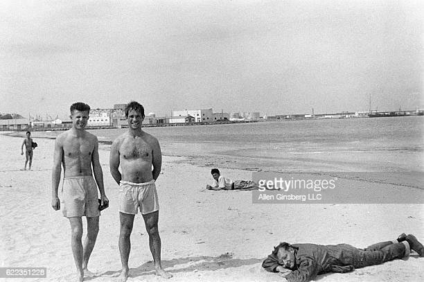 Poets Peter Orlovsky and Jack Kerouac pose in swim trunks converted boxer shorts as William S Burroughs takes a nap fully clothed on a beach in...