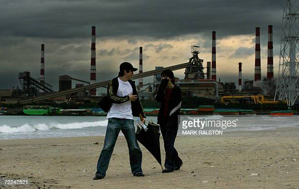 Pohang, REPUBLIC OF KOREA: A South Korean couple enjoy a beach walk during a thunderstorm with the POSCO companies flagship steel mill and...