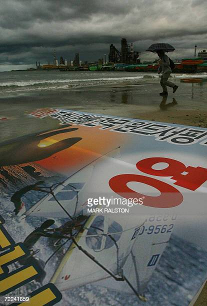 Pohang, REPUBLIC OF KOREA: A South Korean man on a beach walks during a thunderstorm with the POSCO companies flagship steel mill and headquarters in...