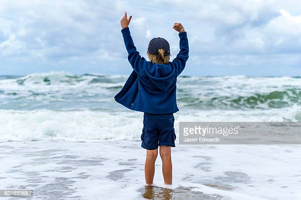 A boy playing in the shallows as storm surge waves roll onto an empty beach.