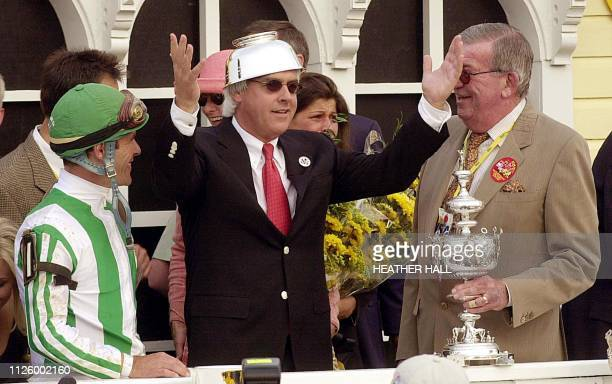 Point Given trainer Bob Baffert puts the winning cup on his head as jockey Gary Stevens and Throughbred Corporation manager Richard Mulhell attend...
