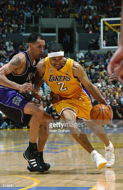 Point guard Derek Fisher of the Los Angeles Lakers drives past guard Doug Christie of the Sacramento Kings during the NBA game at Staples Center in...