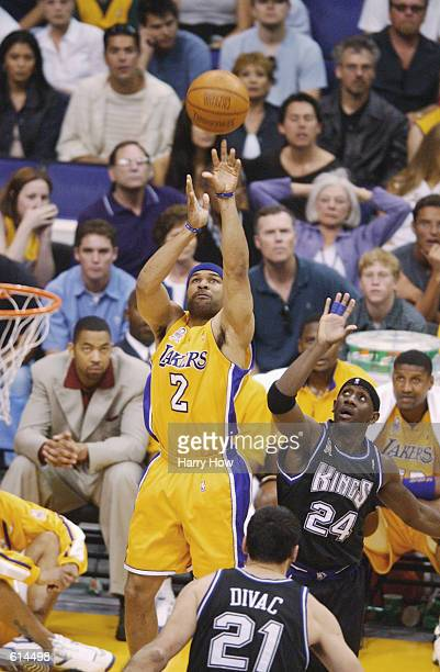 Point guard Derek Fisher of the Los Angeles Lakers shoots over guard Bobby Jackson of the Sacramento Kings during Game four of the Western Conference...